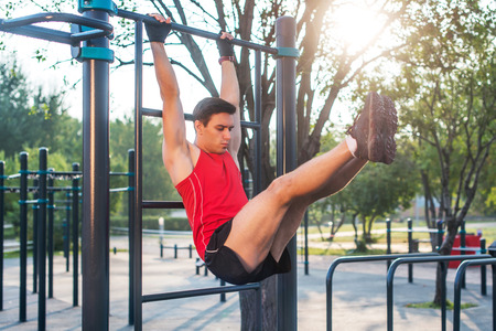 Fitness man hanging on wall bars performing legs raises.