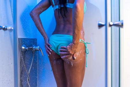Close-up photo of sexy young woman taking a shower wearing bikini in bathroom. Back view tanned female body standing in lingerie in blue light.