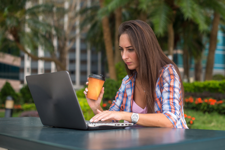 Young woman typing on her laptop working and drinking coffee in the park