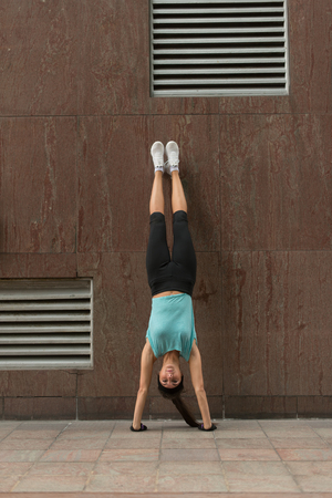 Young woman doing handstand exercise against the wall on the city street.