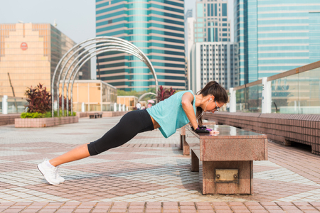 Fitness woman doing feet elevated push-ups on a bench in the city. Sporty girl exercising outdoors 스톡 콘텐츠