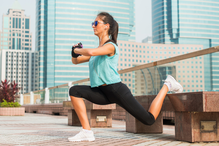 Sporty female athlete doing single leg lunge exercise on bench. Fit young woman working out outdoors in city alley
