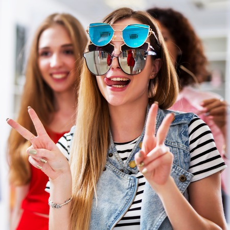 Two girlfriends having fun while doing shopping making faces in the mirror showing V-sign wearing three pair of sunglasses at the same time in womenswear store Stock fotó
