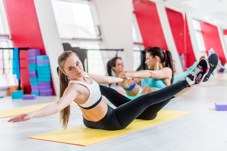 Group of women doing partner stretching exercises during workout session in fitness hall