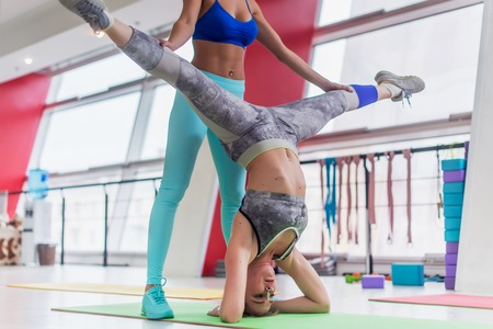 Fit young woman performing yoga headstand leg split with the help of a personal trainer in sports club. Stock Photo
