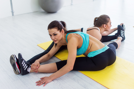 Two slim girls taking part in yoga class working in pair doing partner side seated wide angle pose called parsva upavistha konasana in sports center Stock Photo