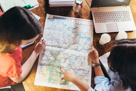 Top view of group of female students studying the map sitting at desk
