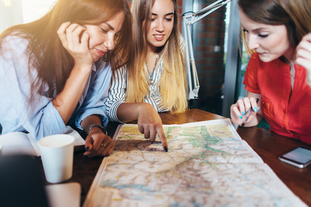 Three girlfriends planning their vacation sitting at table around map choosing the destination Stok Fotoğraf