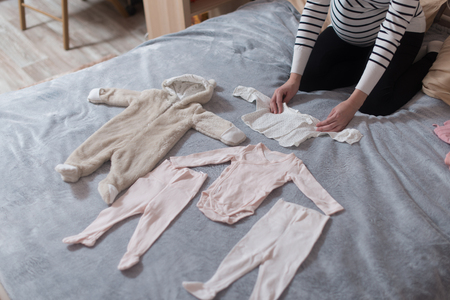 Babys clothes laid out on bed, natural light. Stock Photo - 84734387