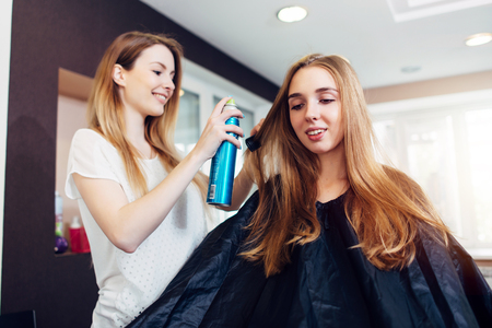 Hairdresser fixing hairstyle of smiling female customer with hair spray in hairdressing beauty salon