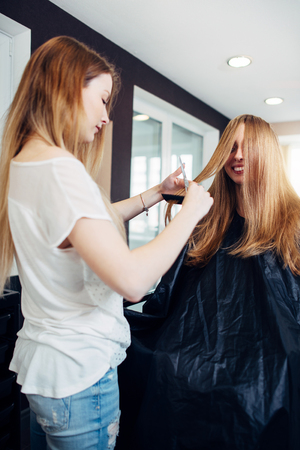Hairdresser is engaged in trimming the split ends of long hair of positive young female client sitting in cape and smiling in beauty shop
