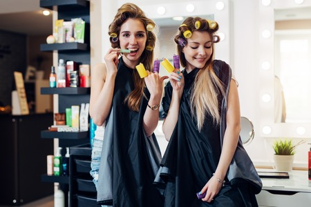 Young pretty girls in capes with hair curlers goofing around in beauty salon. Girlfriends showing devil horn and piece gesture with rollers on fingers having fun together Standard-Bild