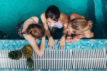 Top view of three female swimmers sitting in a swimming pool resting after training and gossiping