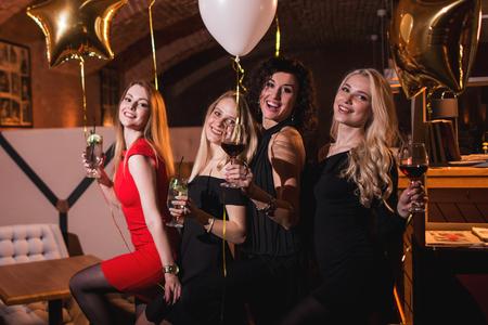 유행의 레스토랑에서 처녀 파티를 갖는 주류를 마시는 칵테일 드레스를 입은 유럽의 여자 친구 웃고