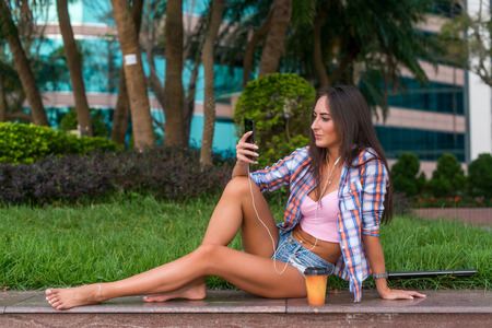 Happy beautiful young woman with bare legs sitting on stone curb in the park and listening to music in headphones. Stockfoto