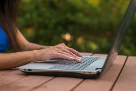 Close-up view of female hands on laptop keyboard. Student learning outdoors. Stock Photo