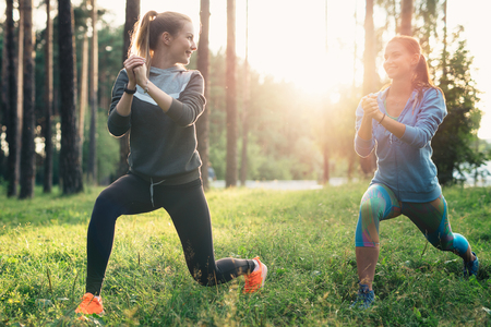 Two athletic female friends wearing jumpsuits doing lunges together training outdoors