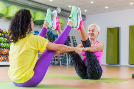 Buddy boat yoga pose by a smiling middle-aged woman and brunette girl sitting backwards in gym Stock Photo