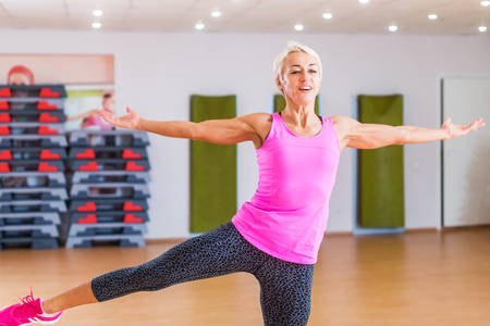 Cheerful muscular blonde middle-aged fitness trainer holding balance on one leg with arms sideward while performing step aerobics dance exercise in gym