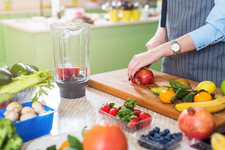 Cropped image of female cook cutting fruit on board preparing smoothie in kitchen Stok Fotoğraf - 88757240