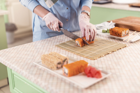 Top view of female chef working in gloves making sushi rolls in restaurant Stock Photo
