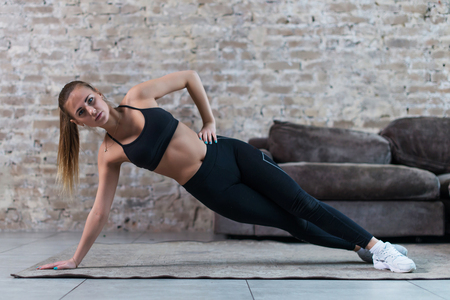Sporty Caucasian girl doing side plank star exercise working abs and oblique muscles indoors against brick wall