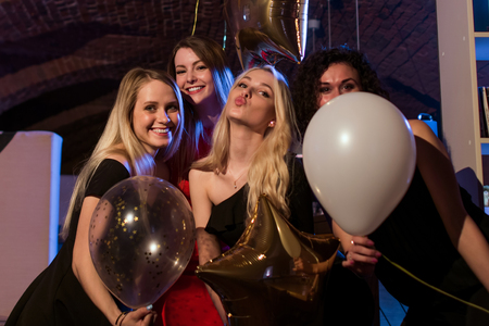 Four beautiful young Caucasian women holding balloons having night out together in trendy bar