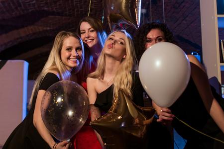 拿着有的气球的四名美丽的年轻白种人妇女有夜在时髦酒吧