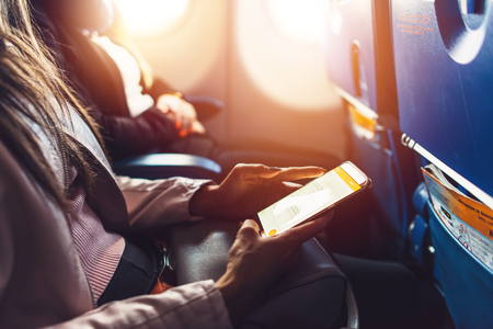 Close-up image of female hands holding smartphone sitting in the airplane Stockfoto