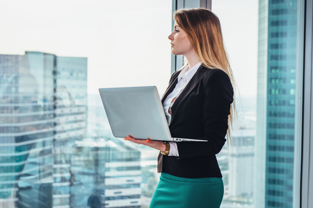 Female journalist writing an article using a laptop thinking standing at window and looking at city business district
