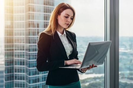 Young female lawyer working in her luxurious office holding a laptop standing against panoramic window with a view on business district