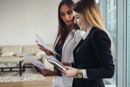 Young estate agent showing apartment and discussing the contract and other documents with a customer