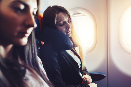Two businesswomen sleeping in the airplane using neck cushion while going on business trip