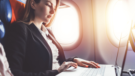 Woman working using laptop while travelling by plane Foto de archivo