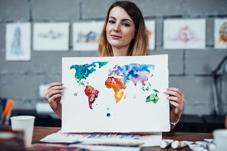 Jonge vrouwelijke illustrator die haar schilderen toont getrokken met waterverftechniek in haar studio