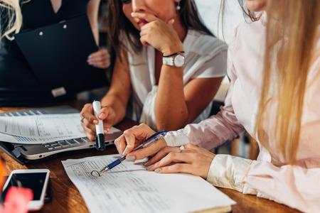 검사 및 사무실에서 책상에 앉아 문서를 가리키는 회계 서류 작업 젊은 여성의 근접 촬영보기