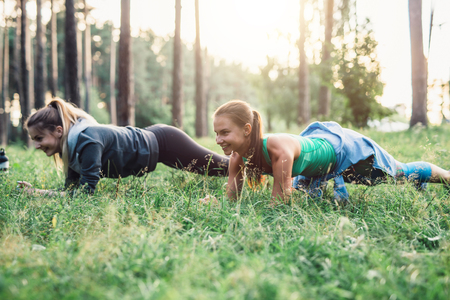 Two girlfriends working out outdoors doing plank exercise on grass