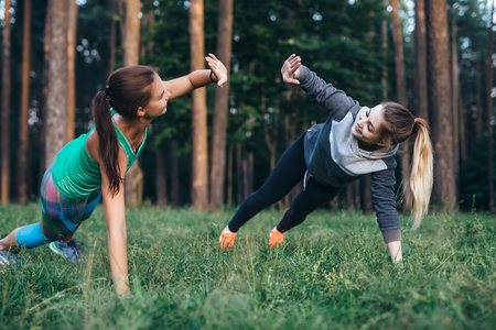 Two female buddies doing partner side plank giving high five while training in the forest