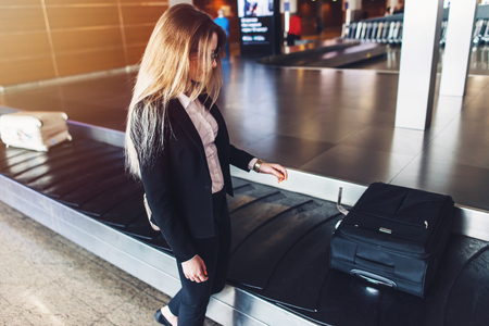 Young businesswoman getting her luggage from baggage claim at airport