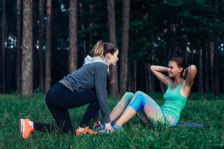 Smiling slim girl doing sit-ups while female friend assisting her holding down the feet. Two girlfriends training together in the forest.