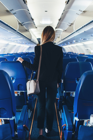 Back view of young woman wearing formal suit walking the aisle on plane