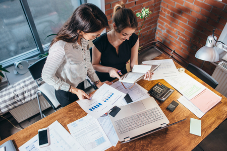 Top view of two female colleagues and desk covered with papers and documents. Businesswomen studying the data working on new sales strategy
