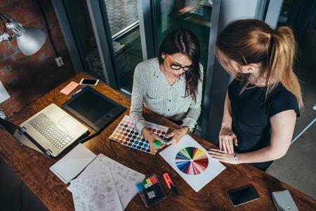 Due creativi personaggi femminili che scelgono i colori che lavorano con tavolozza di colore in ufficio Archivio Fotografico - 89096012