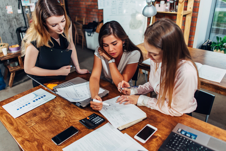 Three female economists checking documentation analyzing documents sitting at desk in modern office