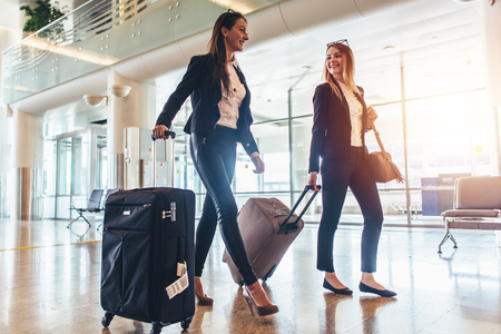 Two stylish female travelers walking with their luggage in airport Stock Photo