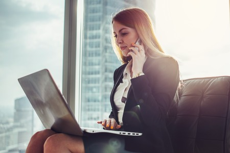 Young woman waiting in a hall sitting in modern office working on laptop talking on the phone Stock Photo