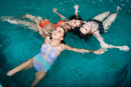 Funny female teenagers fooling around in the swimming pool laughing and enjoying their weekends Stock Photo