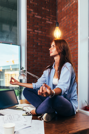 Side view of pretty creative female freelancer sitting in lotus pose on working desk under light bulb waiting for idea to come Stock Photo