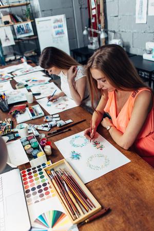 연필로 스케치를 그리는 새로운 프로젝트를 작업하는 두 명의 여성 디자이너 스톡 콘텐츠