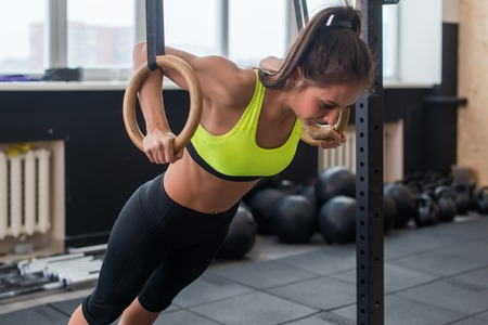 Fitness woman doing push ups training arms with gymnastics rings in the gym Concept workout healthy lifestyle sport.